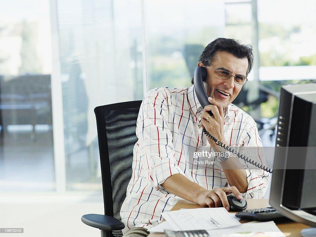 Uomo in ufficio a parlare sul telefono : Foto stock