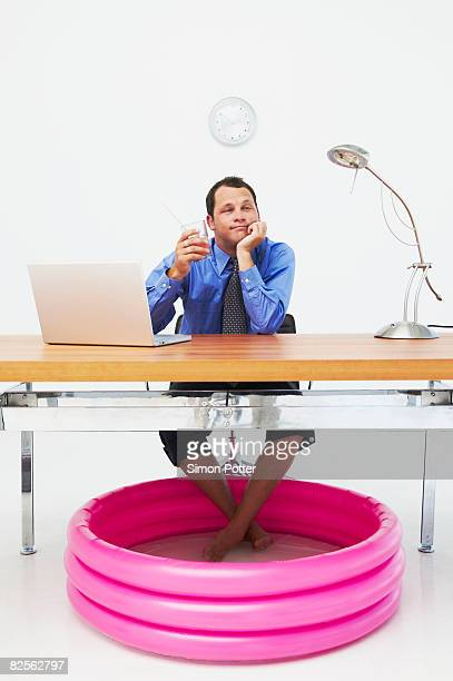 Man in office with feet in paddling pool
