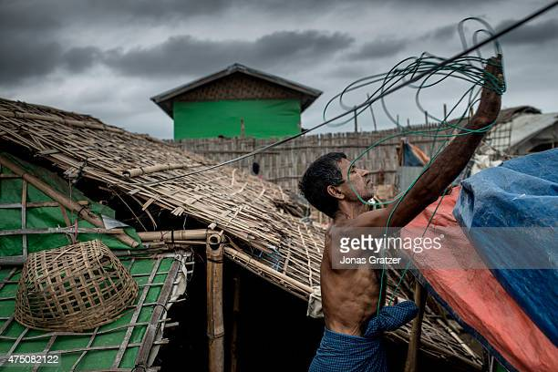 A man in one of the unregistered IDP camp reinforce the roof of his hut for a coming storm May 24 2015 in Sittwe Burma Since 2012 the minority group...