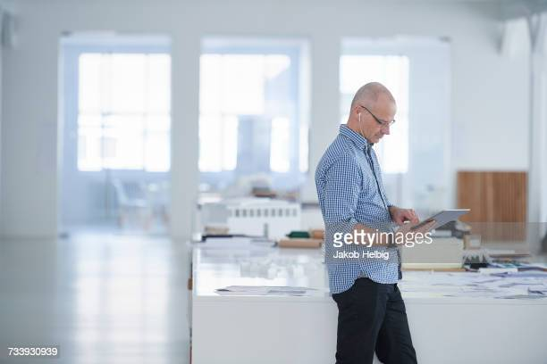 Man in open plan office using digital tablet