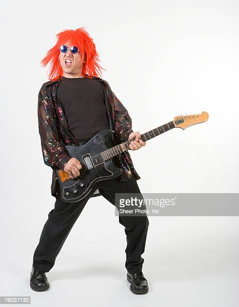 Man in orange hair playing electric guitar, portrait