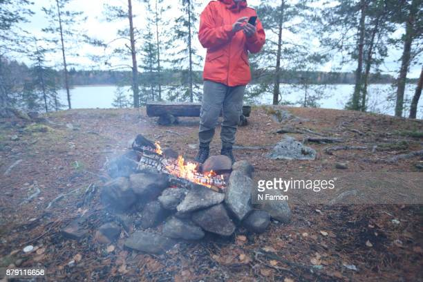 Man in orange jacket on phone by camp fire in Finland