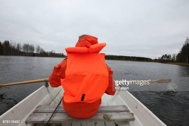 Man in orange jacket rowing