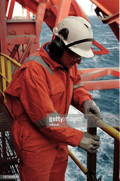 Man in orange uniform and white helmet working on an oil rig