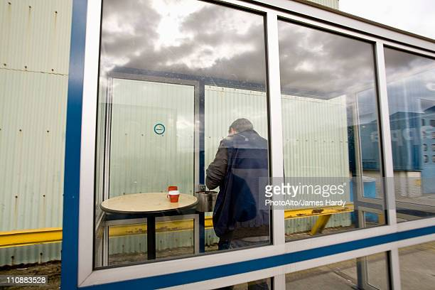 man in outdoor smoking area - windbreak stock pictures, royalty-free photos & images
