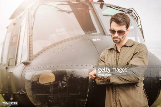 Man in overall next to a helicopter checking the time