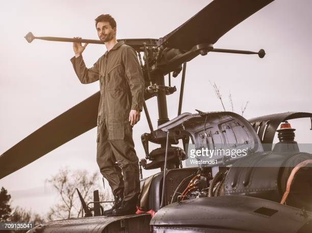 Man in overall standing on top of a helicopter