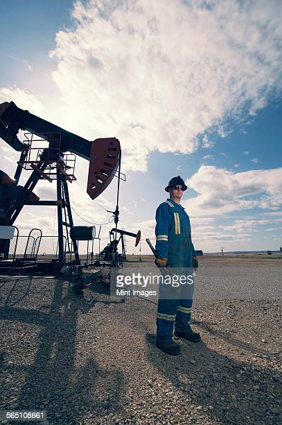 A man in overalls and hard hat at a pump jack in open ground at an oil extraction site.
