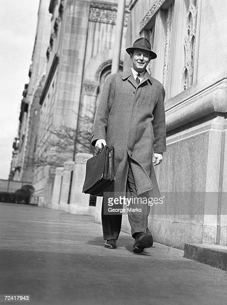 Man in overcoat and hat walking on sidewalk, (B&W), low angle view