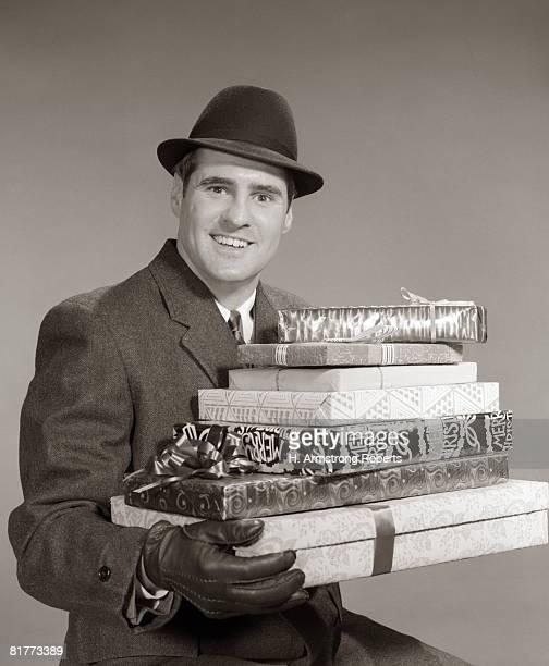 man in overcoat holding stack of christmas presents indoor. - noel noir et blanc photos et images de collection