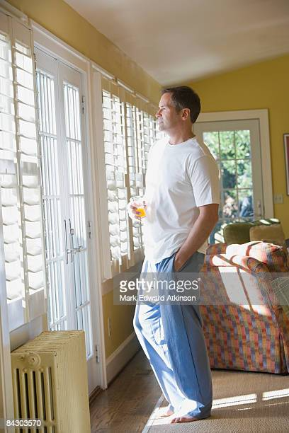 Man in pajamas looking out window