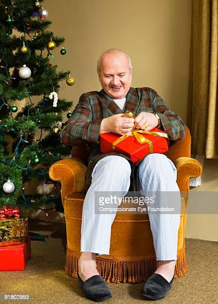 Man in pajamas opening christmas present