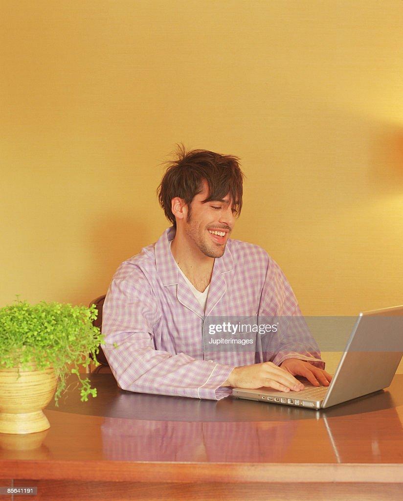 Man in pajamas using laptop computer : Stock Photo