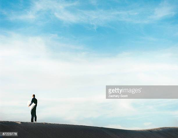 Man in pajamas with pillow in desert