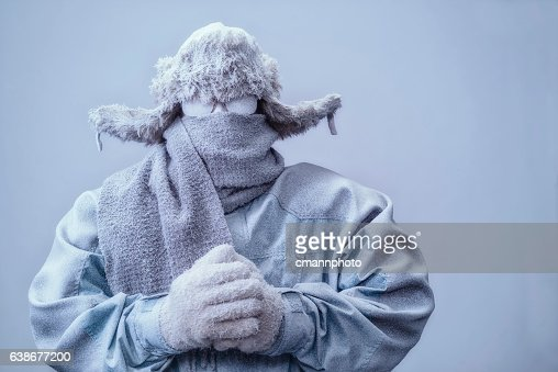 Man in parka, hat and scarf frozen from the cold
