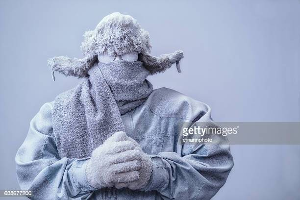 man in parka, hat and scarf frozen from the cold - coat stockfoto's en -beelden