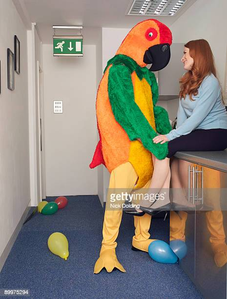 man in parrot outfit with co worker - freaky couples stock photos and pictures