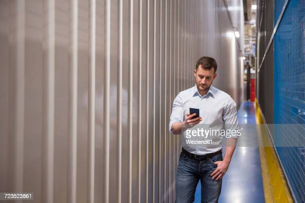 Man in passageway in a factory looking at cell phone