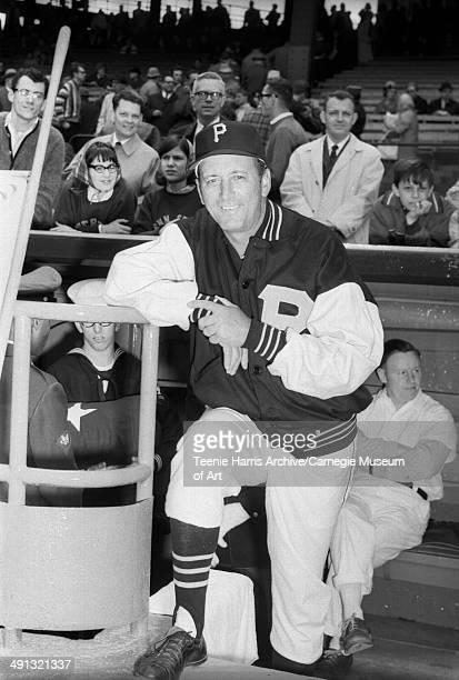 Man in Pittsburgh Pirates baseball uniform wearing dark varsity style jacket posed at dugout steps on Forbes Field for 1965 season opener Pittsburgh...