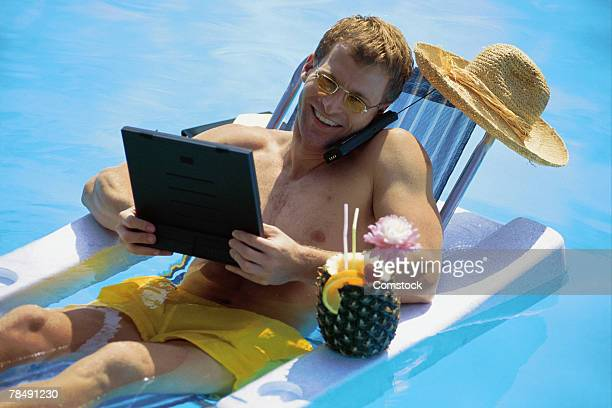 Man in pool, on phone and using laptop