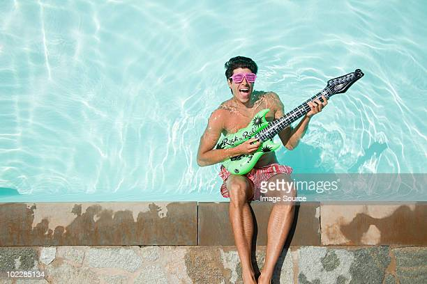 Man in pool with inflatable guitar