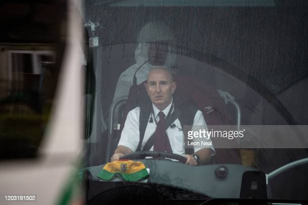 Man in protective clothing sits behind the driver in one of the coaches transporting eighty-three Britons and 27 foreign nationals who have been...