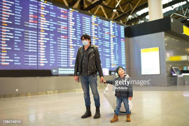 mann in schützender gesichtsmaske und sein kleiner sohn auf dem flughafen während covid-19 pandemie - kid in airport stock-fotos und bilder
