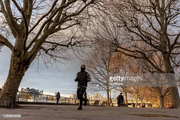 Man in protective face masks is seen exercising by the Thames River as the UK's government introduced strict Coronavirus restrictions earlier this...