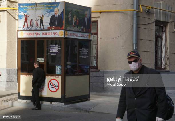 A man in protective mask and gloves passes a security booth with portrait of Russian President Vladimir Putin on the street on October2020 in Central...