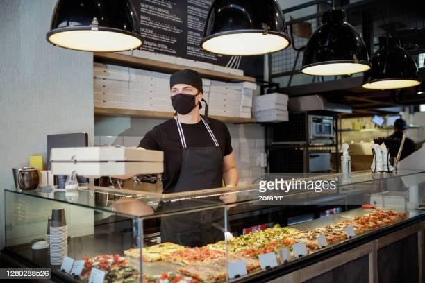 mann in schutzmaske und handschuhen vorbei bestellte pizza in kisten über der glastheke - schnellimbiss stock-fotos und bilder
