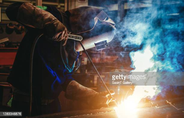 man in protective mask welding metal construction. - fabricage apparatuur stock pictures, royalty-free photos & images