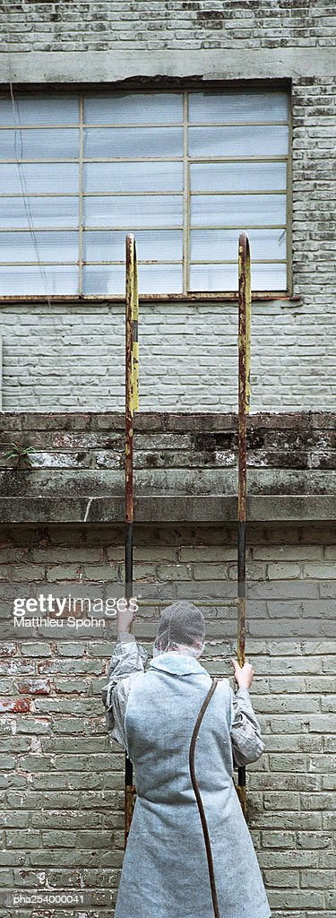Man in protective suit, climbing ladder : Stockfoto