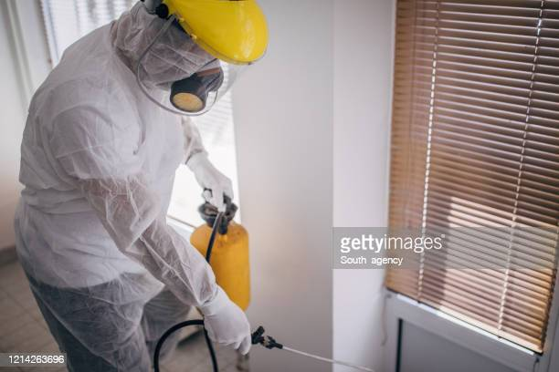 man in protective suit disinfecting and spraying every room in the building - crop sprayer stock pictures, royalty-free photos & images