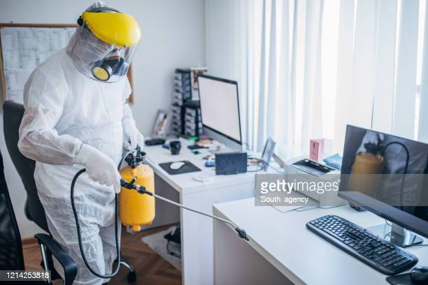 man in protective suit disinfecting office work space - insecticide stock pictures, royalty-free photos & images