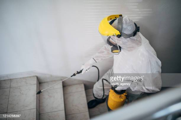 man in protective suit disinfecting steps in building - crop sprayer stock pictures, royalty-free photos & images