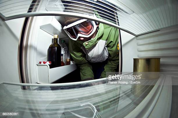 Man In Protective Suit Inspecting Refrigerator