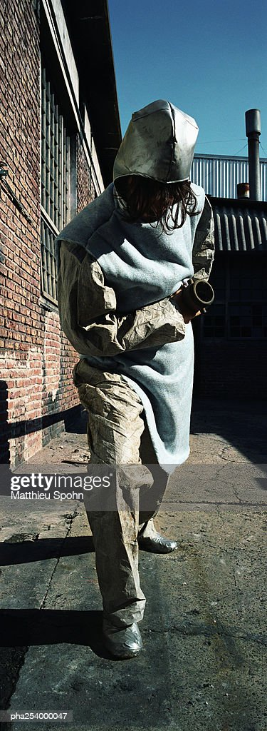 Man in protective suit, pulling tube : Stockfoto