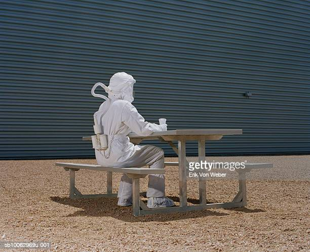 man in protective suit sitting at picnic table - hazmat suit stock pictures, royalty-free photos & images