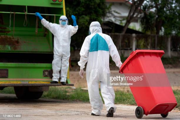 man in protective suit with red infection bin - essential workers stock pictures, royalty-free photos & images