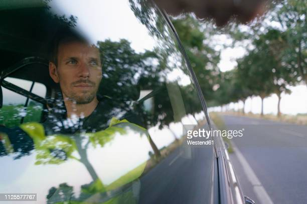 man in protective workwear in a car at country road - reflet photos et images de collection