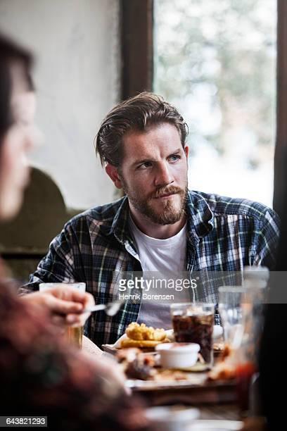 man in pub eating food with friends - comida de pub - fotografias e filmes do acervo