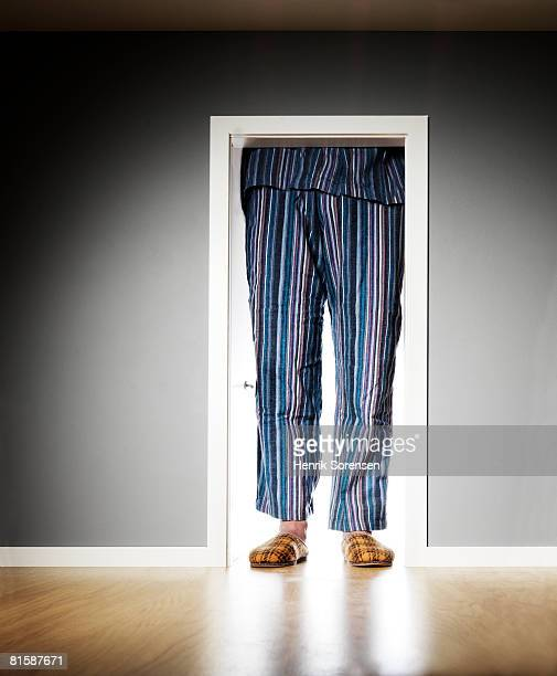 Man in pyjamas standing outside a very small door.