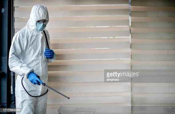 man in quarantine clothes disinfecting room - prevention stock pictures, royalty-free photos & images