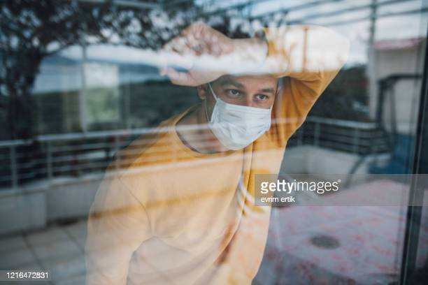 man in quarantine wearing a mask and looking through the window - obscured face stock pictures, royalty-free photos & images