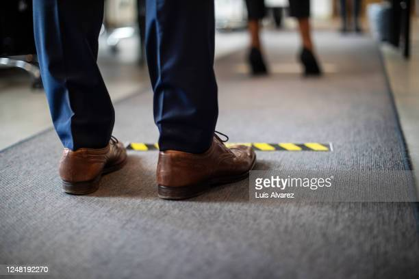 man in queue at office for safe entry checks - ver stockfoto's en -beelden