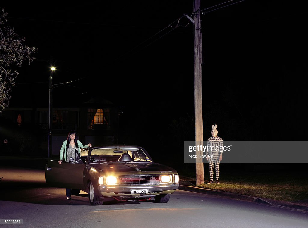 Man in rabbit mask watches woman in car : Stock Photo