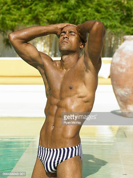 man in racing briefs beside swimming pool, hands behind head - black men in speedos stock photos and pictures