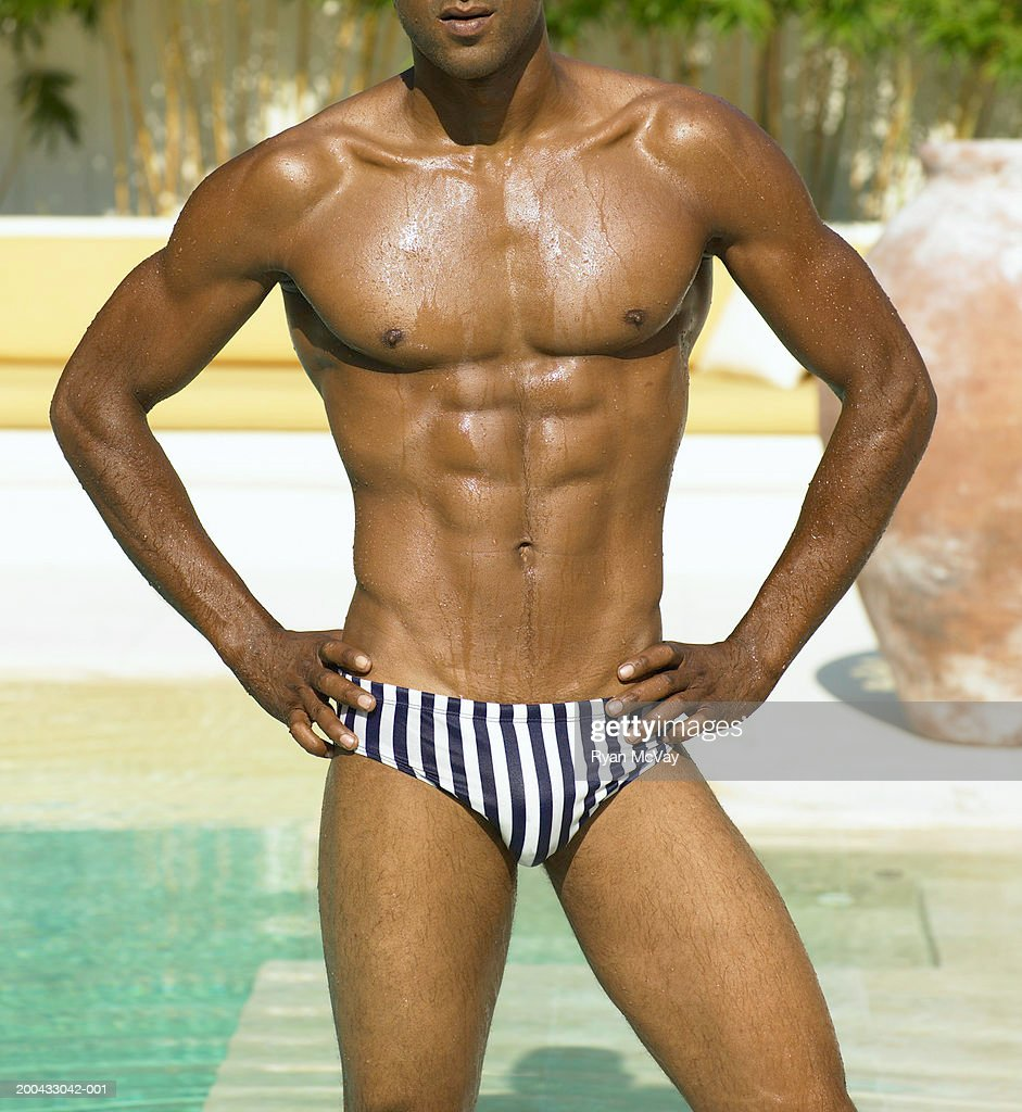 Man in racing briefs standing beside pool, hands on hips, mid section : Stock Photo