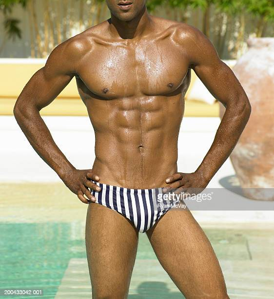 man in racing briefs standing beside pool, hands on hips, mid section - black men in speedos stock photos and pictures