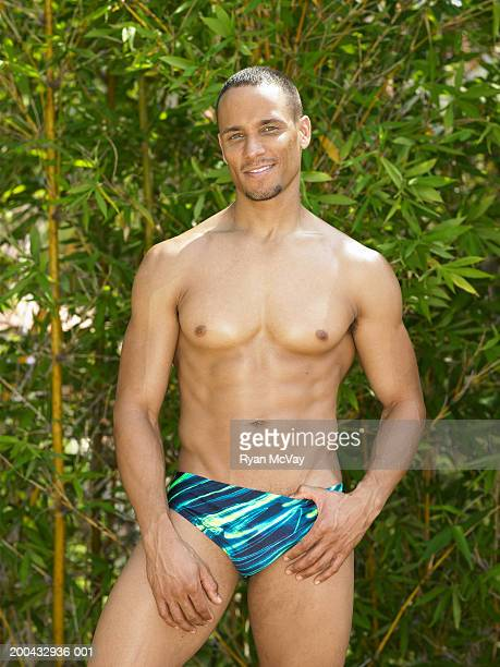 man in racing briefs standing in front of bamboo, smiling, portrait - black men in speedos stock photos and pictures